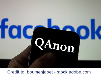 QAnon organization logo seen on the smartphone which is placed on Facebook logos. Credit: boumenjapet - stock.adobe.com